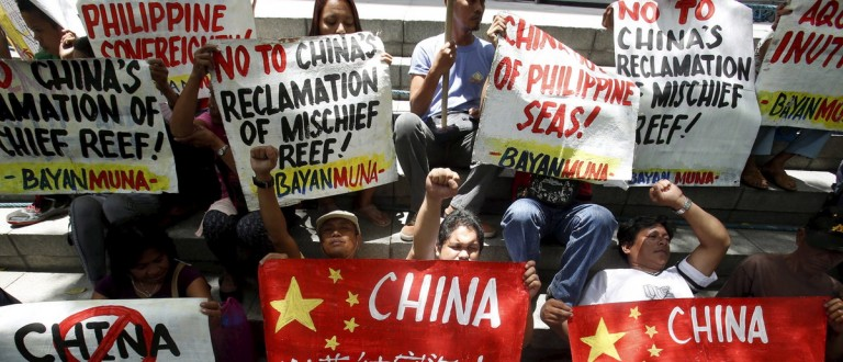 Members of Bayan Muna (Country First) Party List group display placards during a picket rally over territorial dispute with China in South China Sea, outside the Chinese Consulate in Makati, Metro Manila April 17, 2015. Philippine President Benigno Aquino said on Friday the territorial dispute with China in the South China Sea was of concern for the world because global trade will be hit by China's reclamation. Recent satellite images show China has made rapid progress in building an airstrip suitable for military use in contested territory in the Spratly Islands and may be planning another, moves that have been greeted with concern in the United States and Asia. REUTERS/Erik De Castro