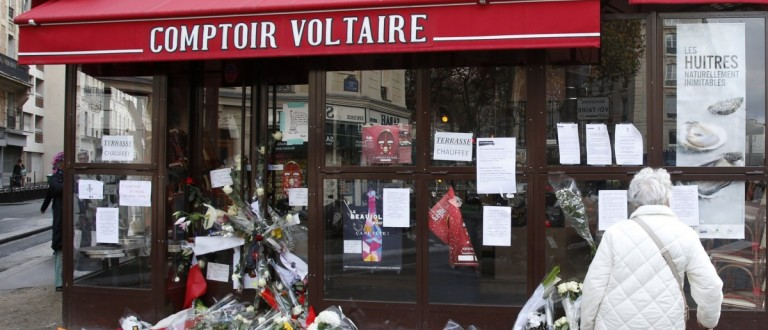 A woman stops to look at flowers, candles and messages in tribute to victims in front of the Comptoir Voltaire cafe, one of the sites of the deadly attacks in Paris, France, November 17, 2015.   REUTERS/Jacky Naegelen