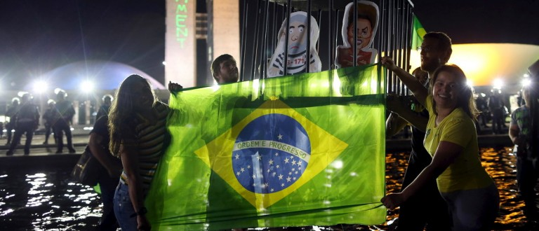 """Demonstrators display inflatable dolls of Brazilian President Dilma Rousseff and former President Luiz Inacio Lula da Silva during a protest against Rousseff in front of the National Congress in Brasilia, Brazil, March 21, 2016. The twin congressional office towers show a laser message that reads """"Impeachment"""". REUTERS/Adriano Machado"""