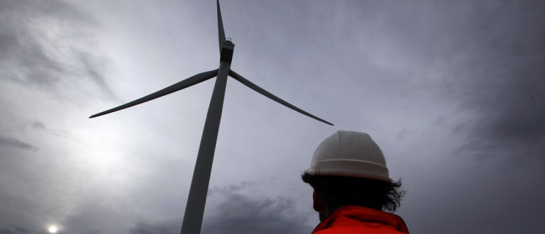 David Brockwell walks between wind turbines during a routine inspection at the Infigen Energy wind farm located on the hills surrounding Lake George, 50 km north of the Australian capital city of Canberra May 13, 2013. Infigen Energy's Capital Windfarm, built five years ago, was a vanguard for wind power as Australia sought to wean itself from cheap fossil-fuel power in the face of climate shift blamed in part for Lake George's transformation to a vast plain. But big plans to expand the Infigen renewable energy project near Canberra and others like it have been put on hold awaiting the outcome of an election in September. The ballot, which opinion polls show the opposition conservatives winning, along with an economic slowdown and rising home energy bills have put the brakes on Australia's decade-long clean energy push. At stake in the Sept. 14 vote is a controversial carbon trading scheme championed by ruling Labor to curb greenhouse gas emissions, with a $20 billion pipeline in renewable investment largely on hold as nervous companies sit on their hands. Picture taken May 13, 2013. REUTERS/David Gray