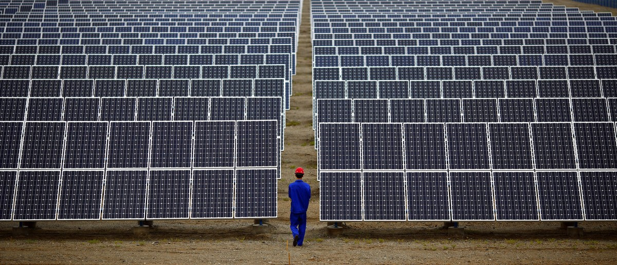 A worker inspects solar panels at a solar Dunhuang, 950km (590 miles) northwest of Lanzhou, Gansu Province September 16, 2013. China is pumping investment into wind power, which is more cost-competitive than solar energy and partly able to compete with coal and gas. China is the world's biggest producer of CO2 emissions, but is also the world's leading generator of renewable electricity. Environmental issues will be under the spotlight during a working group of the Intergovernmental Panel on Climate Change, which will meet in Stockholm from September 23-26. (REUTERS/Carlos Barria)