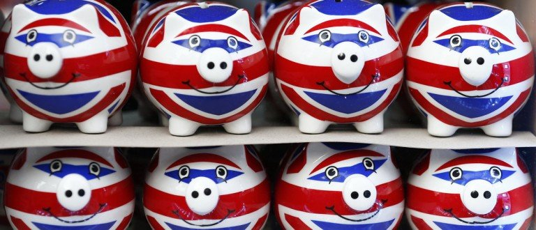 Smiling Union Jack piggy banks are lined up for sale in the window of a souvenir store on Oxford Street in central London January 20, 2014. Britain's financial services industry is beginning to feel the benefits of economic recovery, as firms report growth in profits, business volumes and optimism in the fourth quarter, according to a survey. Some 69 percent of firms said they felt more optimistic about the overall business situation versus just 1 percent who felt less optimistic, the quarterly CBI/PwC financial services survey showed on Monday. REUTERS/Andrew Winning