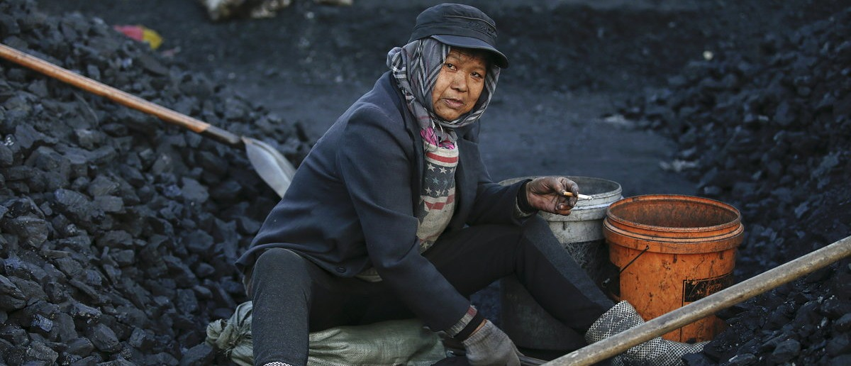 A villager is pictured as she selects coal at local businessman Sun Meng's small coal depot near a coal mine of the state-owned Longmay Group on the outskirts of Jixi, in Heilongjiang province, China, October 23, 2015. REUTERS/Jason Lee