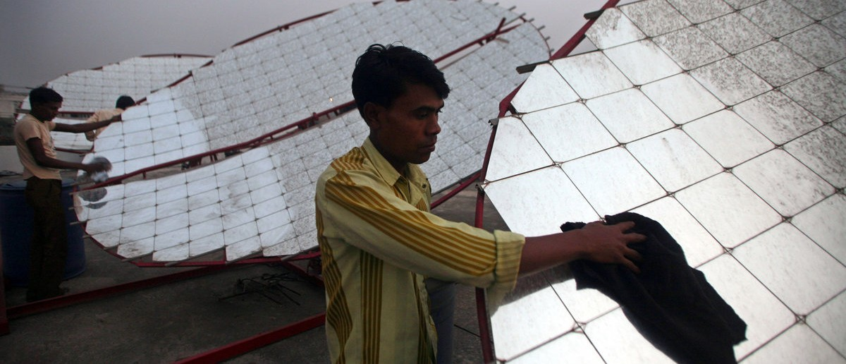 Workers clean solar concentrator panels (solar parabolic dish) at the Tapi solar food processing unit at Kapodra village, about 350 km (220 miles) south of the western Indian city of Ahmedabad, December 16, 2009. REUTERS/Amit Dave