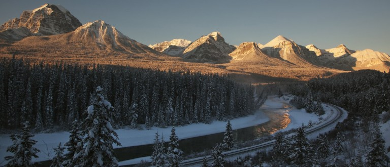 A mountain range is bathed by the dawn sun in Lake Louise, Alberta November 24, 2010. REUTERS/Andy Clark