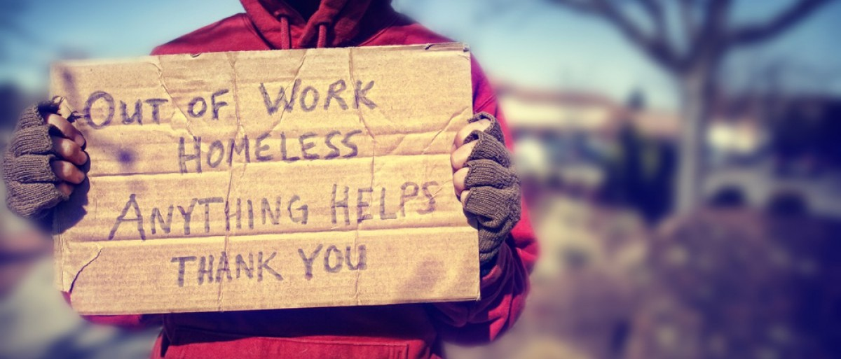 Homeless person holds cardboard sign. (Credit: Annette Shaff/Shuttershock)