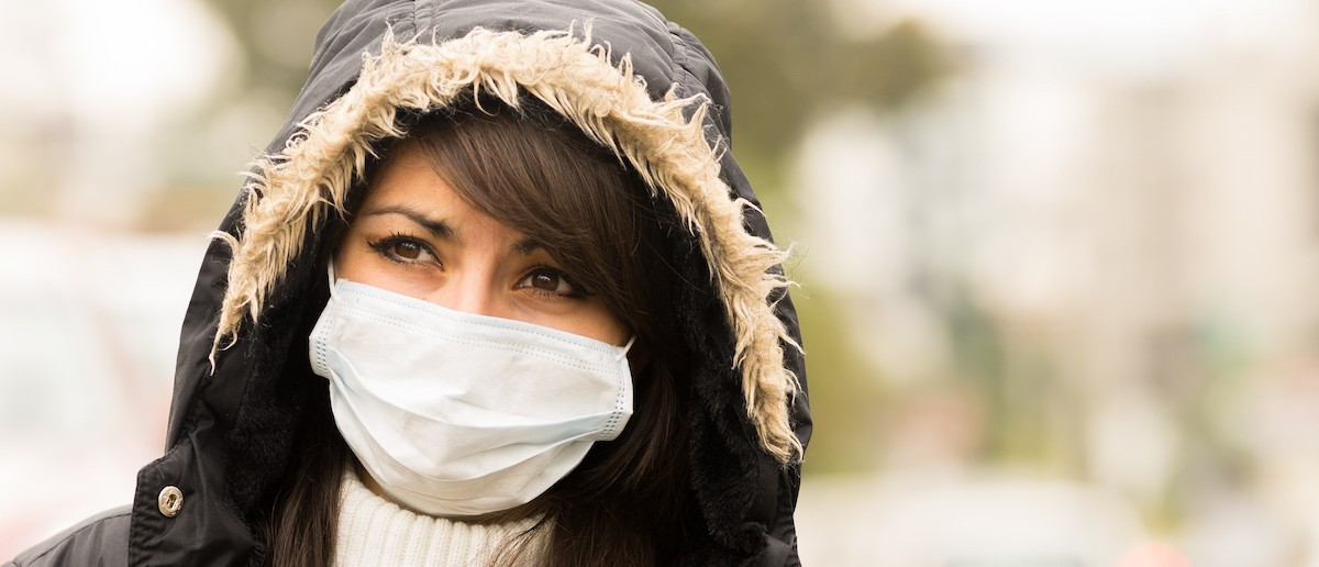 Portrait of young girl walking wearing jacket and a mask in the city. (Shutterstock)