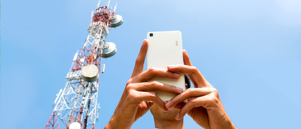 Man uses smartphone with telecommunications tower in the background. Source: foto500/Shutterstock