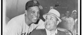 Willie Mays, standing, wearing baseball uniform, with arm around shoulders of Roy Campanella, seated