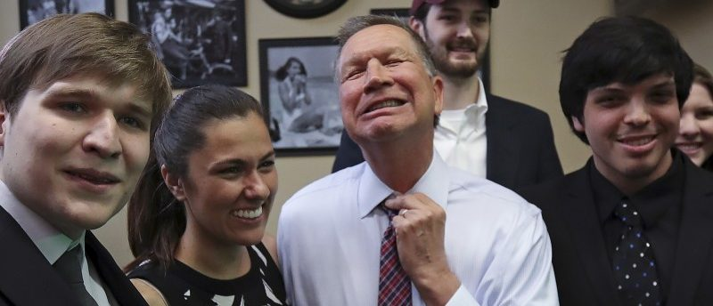 Republican presidential candidate John Kasich adjusts his tie as he poses for a photo with supporters before a meet and greet at the Arthur Avenue Market in the Bronx borough of New York April 7, 2016. REUTERS/Carlo Allegri