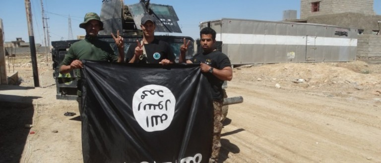 Iraqi security forces stand with an Islamic State flag which they pulled down in the town of Hit in Anbar province, April 2, 2016. REUTERS/Stringer