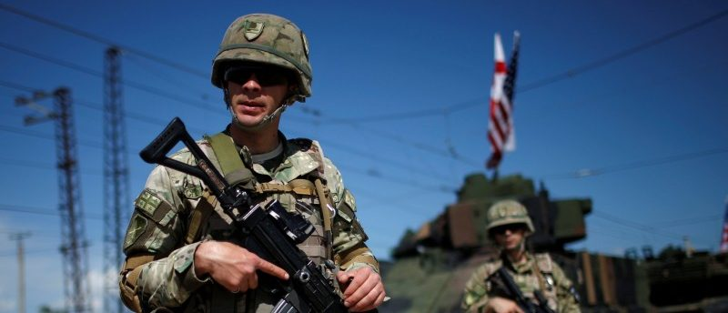 Georgian servicemen stand in front of U.S. military vehicles upon the joint U.S.-Georgian exercise Noble Partner 2016 in Vaziani