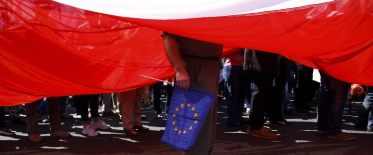 A man stands under a giant Polish flag during anti-government demonstration organized by main opposition parties in Warsaw