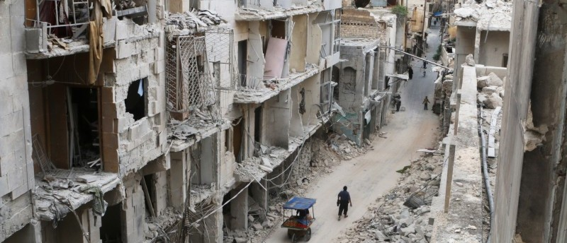 Residents walk near damaged buildings in the rebel held area of Old Aleppo