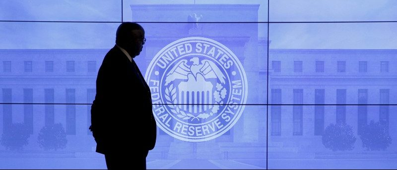 A guard walks in front of a Federal Reserve image before press conference in Washington