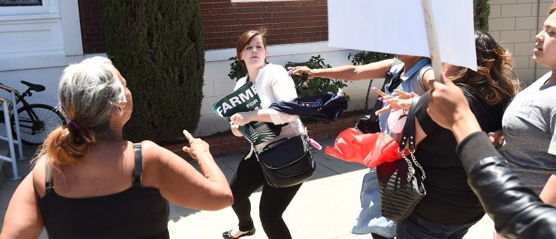 Protesters confront a woman, center, leaving a rally for Republican U.S. presidential candidate Donald Trump in Fresno, California, U.S. May 27, 2016. REUTERS/Noah Berger