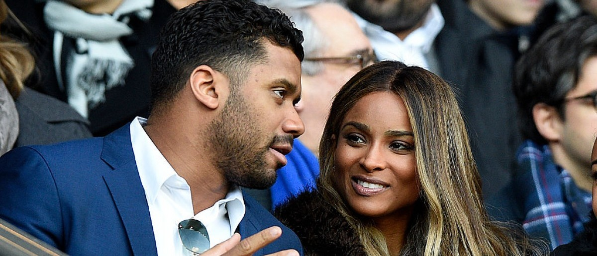 The Seattle Seahawks' quarterback Russell Wilson (L) speaks to his girlfriend singer Ciara during the French L1 football match between Paris Saint-Germain (PSG) and Montpellier (MHSC) on March 5, 2016, at the Parc des Princes stadium in Paris. (FRANCK FIFE/AFP/Getty Images)