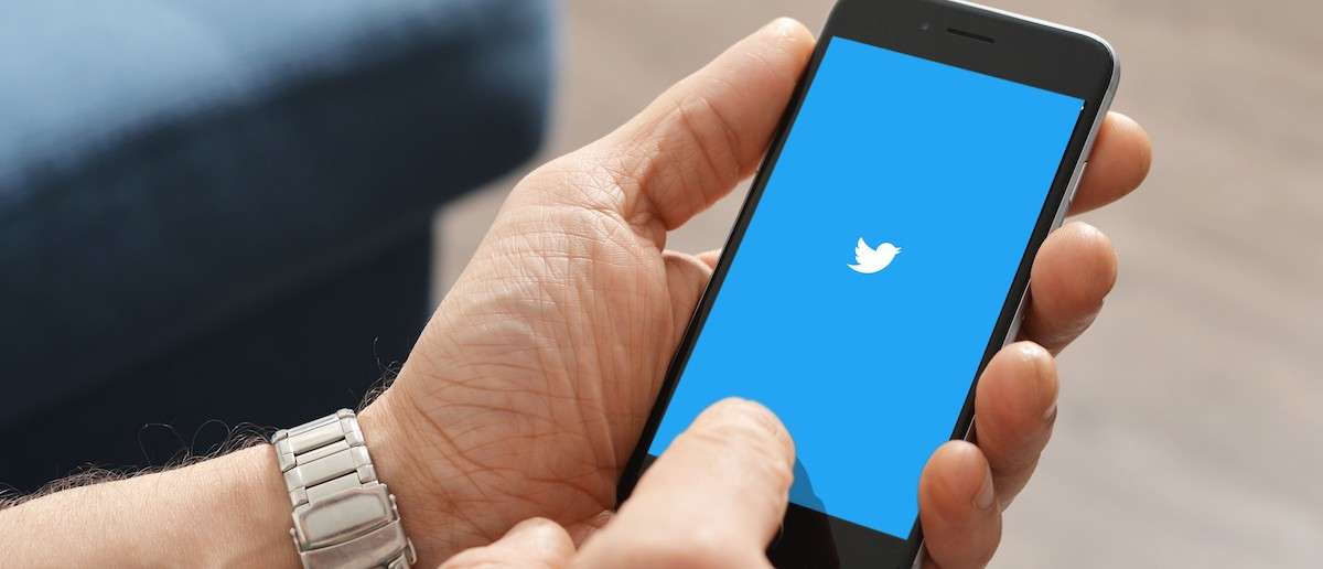 A man using Twitter app on Apple iPhone 6. Twitter is an online social networking service that enables users to send and read short messages called %22tweets%22 (Credit: Shutterstock/mama_mia)