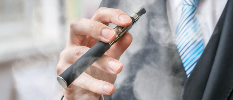 Businessman holds vaporizer and is smoking electronic cigarette.