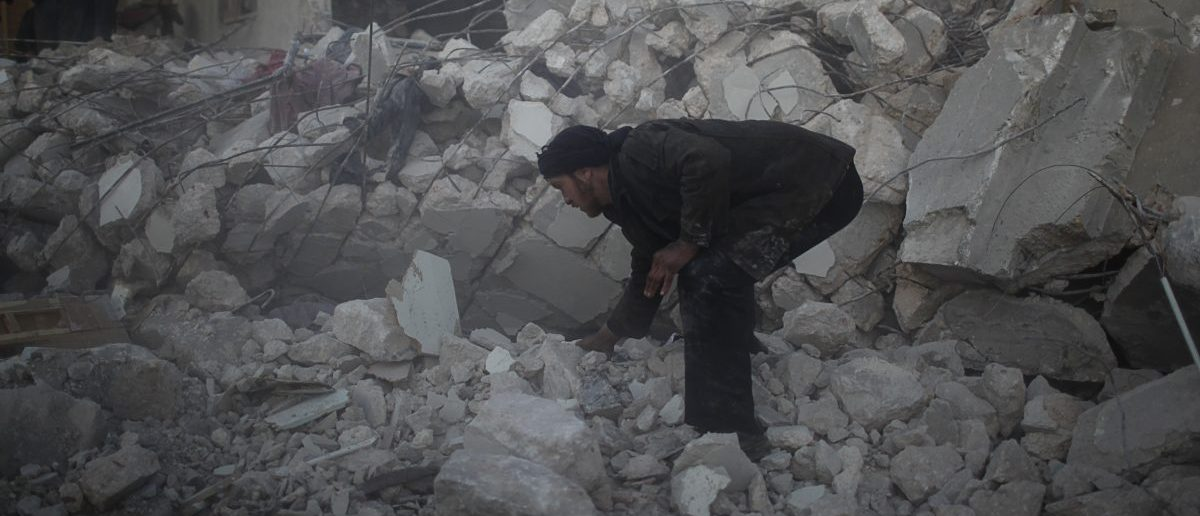 "A man searches for survivors after an air strike by a fighter jet loyal to Syrian President Bashar al-Assad in Azaz city, North Aleppo, December 29, 2012. Syria faces ""hell"" if no deal is struck to end 21 months of bloodshed, an international mediator said on Saturday, but his talks in Russia brought no sign of a breakthrough after a week of intense diplomacy. REUTERS/Ahmed Jadallah"