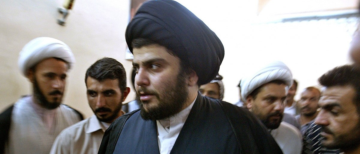 Iraqi Shi'ite cleric Moqtada Al-Sadr (C) arrives at a news conference held inside the shrine of Imam Ali in the holy city of Najaf, May 12, 2004. Rebel Shi'ite cleric Moqtada al-Sadr vowed Wednesday to press on with his fight against the U.S.-led occupation of Iraq but said he would disband his Mahdi Army militia if Shi'ite leaders asked him to. REUTERS/Faleh Kheiber