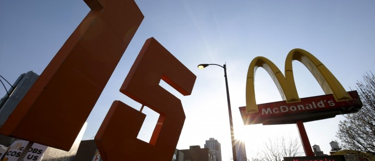 Demonstrators march past a McDonald's (REUTERS/Jim Young)