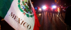Trump Protester waves Mexican flag in front of police (Reuters Pictures)