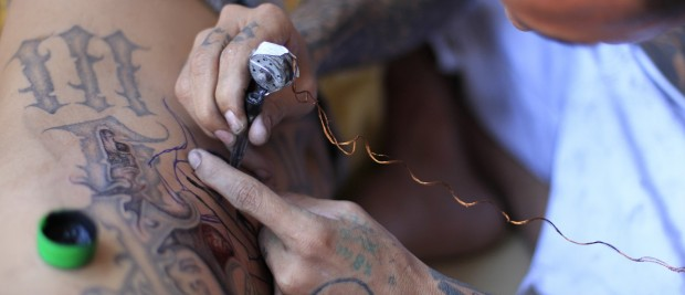 A jailed gang member gets a tattoo done by a fellow inmate at the maximum security jail of Izalco in Sonsonate