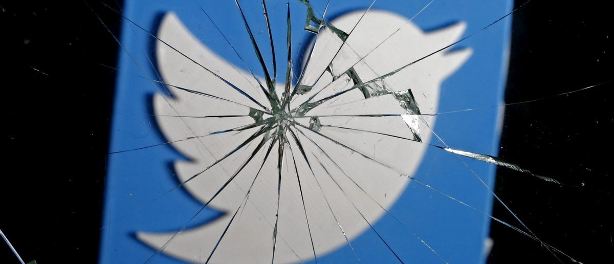 A 3D-printed Twitter logo is seen through broken glass, in this picture illustration taken February 8, 2016. Twitter shed 5.4 percent to hit a new record low of $14.87 after reports over the weekend that the company was planning to change how it display tweets. REUTERS/Dado Ruvic/Illustration - RTX261LE
