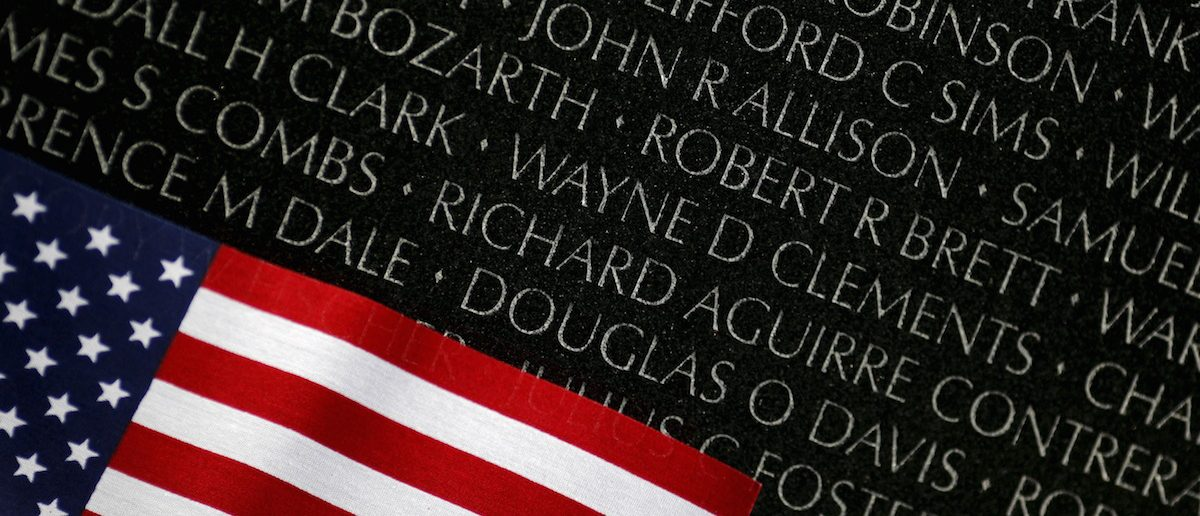 A U.S. flag is seen next to the names etched in black granite at the Vietnam Veterans Memorial wall during Veterans day in Washington
