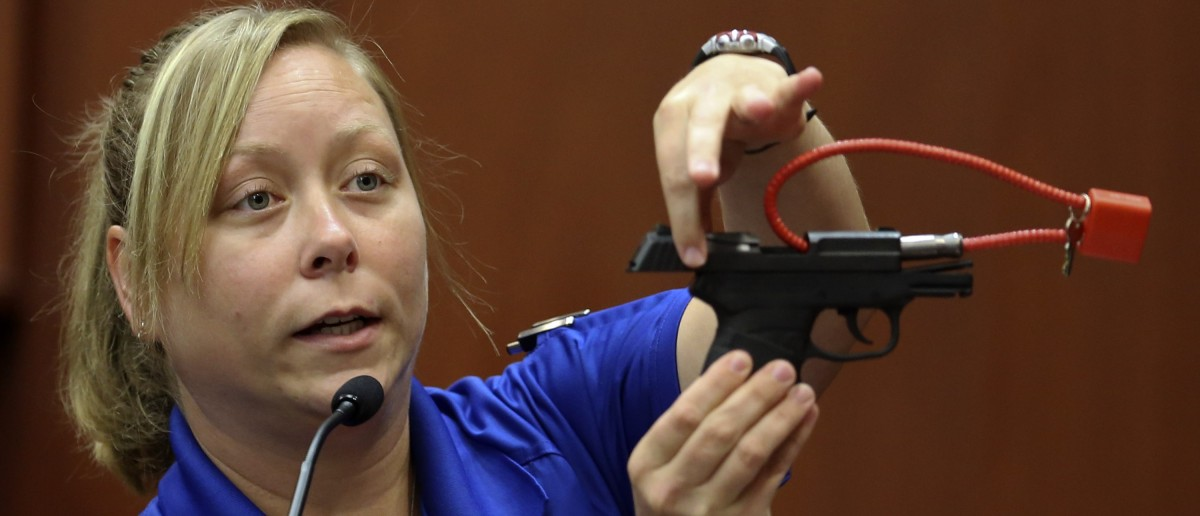SANFORD, FL - JUNE 25: Diana Smith, crime scene technician for the Sanford Police Department, shows the jury a gun that was collected as evidence at the crime scene, during George Zimmerman's trial in Seminole circuit court June 25, 2013 in Sanford, Florida. Zimmerman is charged with second-degree murder for the February 2012 shooting death of 17-year-old Trayvon Martin. (Photo by Gary W. Green-Pool/Getty Images)