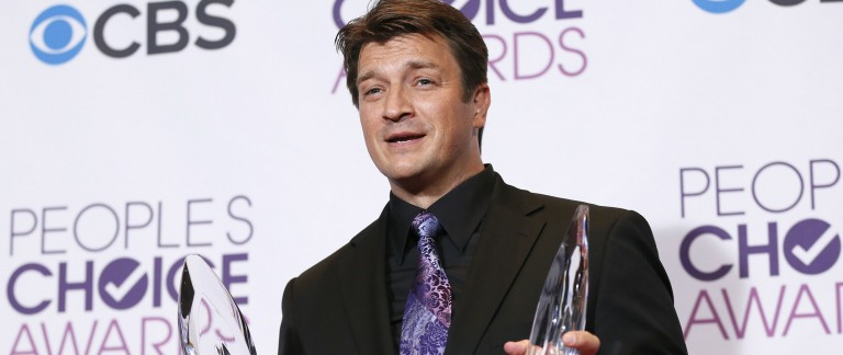 Actor Nathan Fillion holds awards backstage at the 2013 People's Choice Awards in Los Angeles (photo:Reuters/Danny Moloshok)