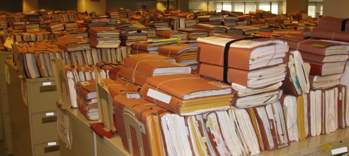 Messy stacks of paper medical records as a VA facility. US government photo from VA IG report https://veteransnewsblog.files.wordpress.com/2012/08/vaoig-12-00244-241.pdf