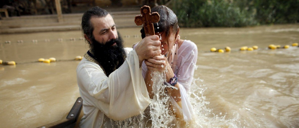 A Christian pilgrim is baptised as she takes part in a ceremony at the baptismal site known as Qasr el-Yahud on the banks of the Jordan River, near the West Bank city of Jericho January 18, 2016. Thousands of Orthodox Christians flocked to the Jordan River to celebrate the feast of the Epiphany at the traditional site where it is believed John the Baptist baptised Jesus. REUTERS/Nir Elias