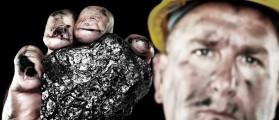 A dirty coalminer displays a lump of coal as a power and energy source. Shutterstock/Joe Belanger