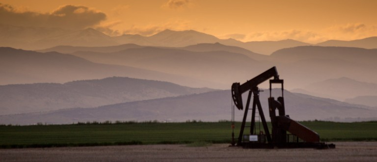 Front range of oil pumpjack with crepuscular rays and dramatic clouds. Shutterstock / Bridget Calip