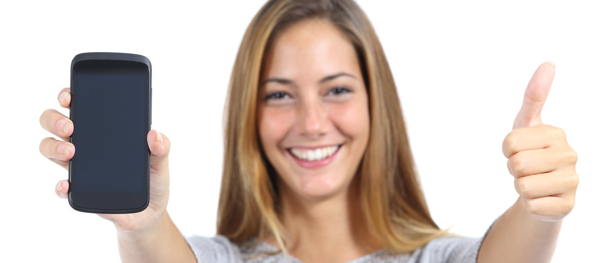 Woman showing a smart phone with thumb up isolated on a white background. Shutterstock/Antonio Guillem
