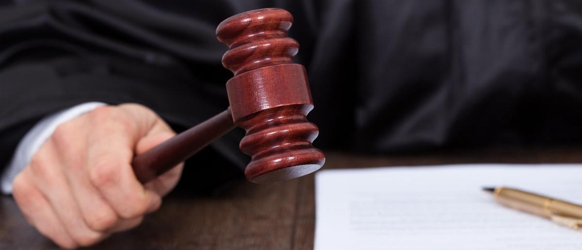Judge giving verdict by hitting mallet at desk. Shutterstock/Andrey Popov