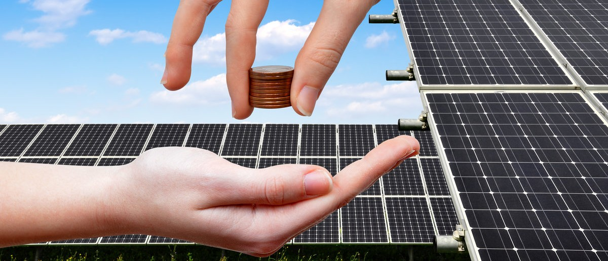Female hands with money. In the background solar panel. (Shutterstock.com/ Vaclav Volrab)