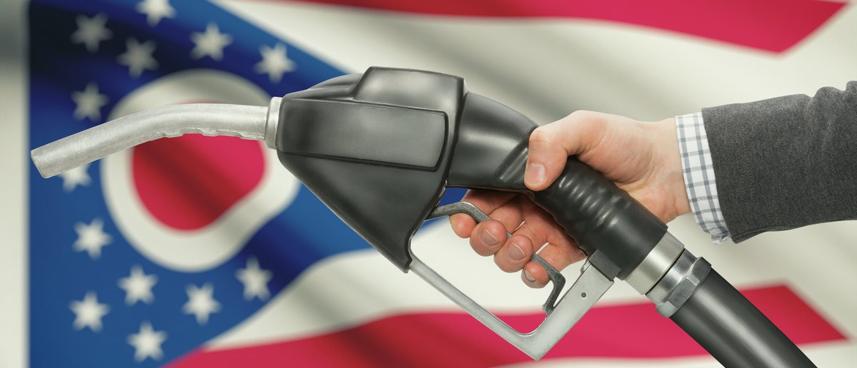 Fuel pump nozzle in hand with US states flags on background - Ohio Shutterstock.com / Niyazz