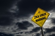 Zika virus warning sign against a stormy background with dirty and angled sign for drama. (Shutterstock.com / Ronnie Chua)