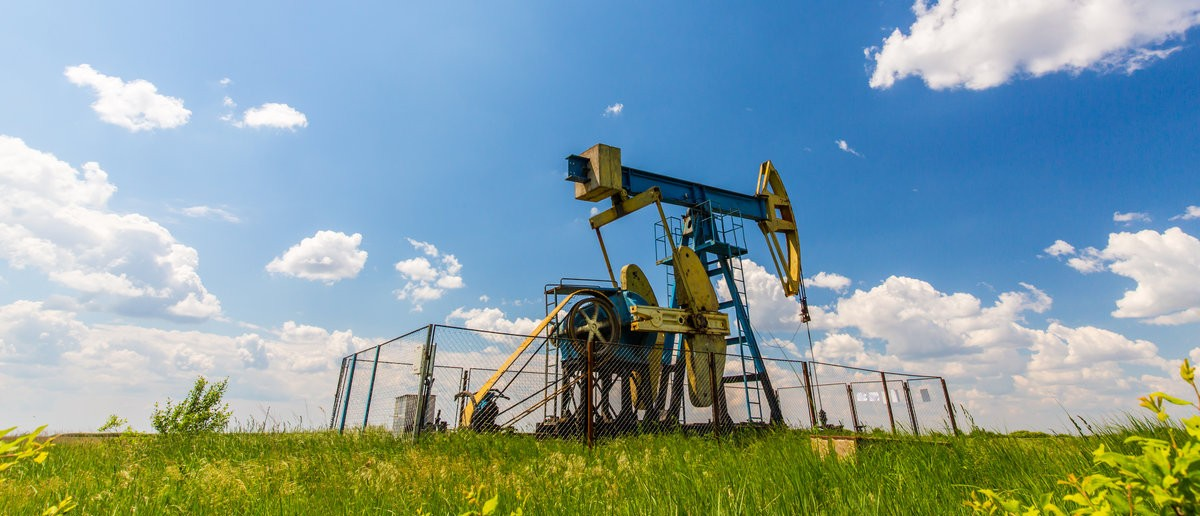Oil and gas well profiled on blue sky with cumulus clouds.