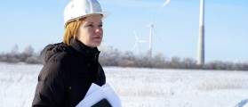 Woman engineer or architect with white safety hat and wind turbines on background. Shutterstock.com / nostal6ie