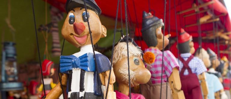Wooden puppet group in a market stall. (Shutterstock/Bykofoto)