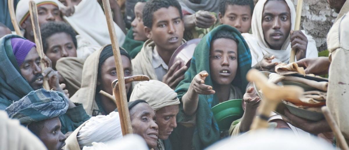 LALIBELA, ETHIOPIA - JANUARY 7: Unidentified volunteers hand out food to pilgrims after celebration of Orthodox Christmas on January 7, 2014, Lalibela, Ethiopia. Lalibela is overcrowded on Christmas. (Vlad Karavaev / Shutterstock.com)