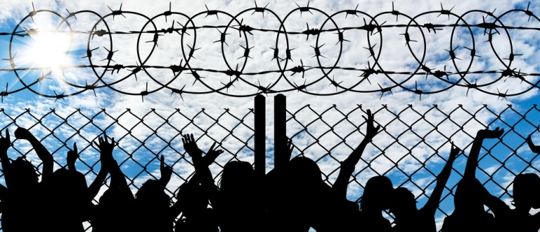 Silhouette of refugees behind metal bars and barbed wire (Credit: Prazis/Shutterstock)
