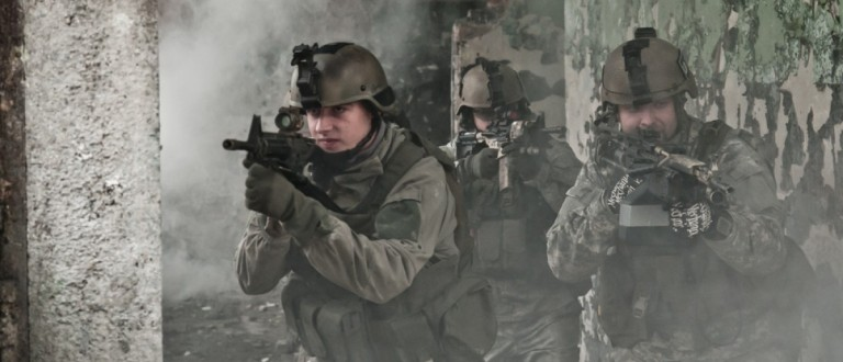 A group of soldiers clear a room through smoke. Source: Przemek Tokar/Shutterstock