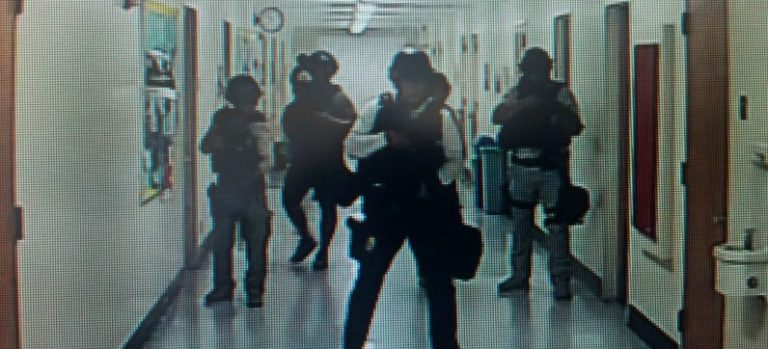 Police officers search corridors and rooms after the report of an active shooter on a UCLA campus in Los Angeles, California, U.S. June 1, 2016 in a still image from a CCTV camera