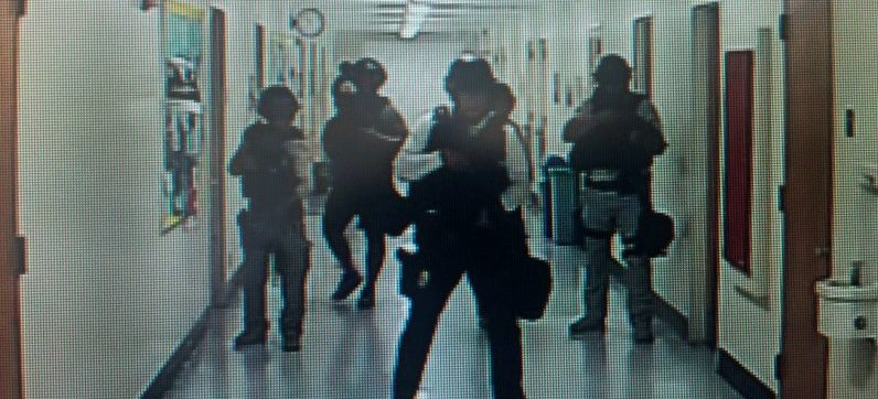 Police officers search corridors and rooms after the report of an active shooter on a UCLA campus in Los Angeles, California, U.S. June 1, 2016 in a still image from a CCTV camera. Kara Leung/UCLA/Handout via REUTERS