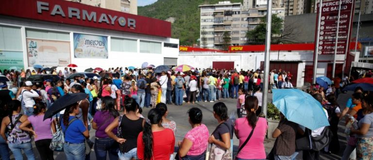 People line up to try to buy toilet paper and diapers outside a pharmacy in Caracas